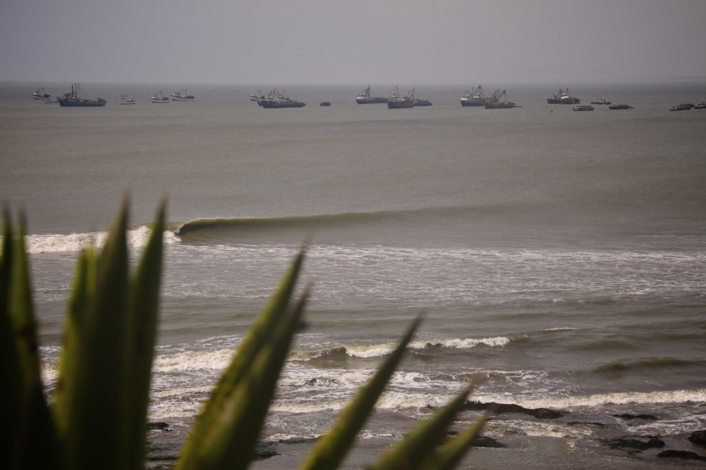 onda quebrando no mar com barcos ao fundo no peru, chicama, no peru, welcome surf trips